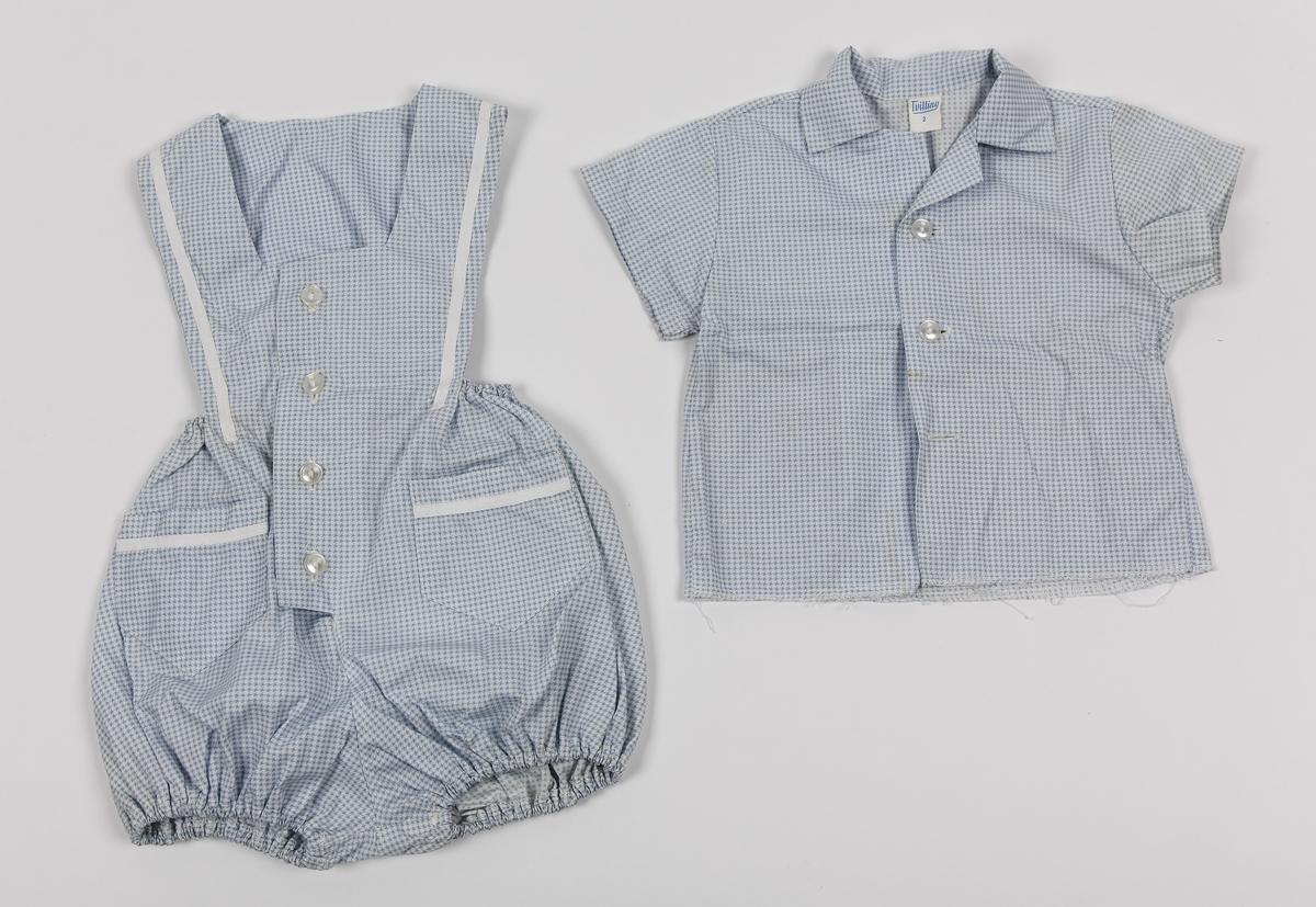 A: Barnebukse. Korte ben, strikk i livet og benåpning, smekke foran og bak. To lommer. Hvite bånd på lommer og smekke. Smårutet mønster. B: Barneskjorte. Korte ermer. Smårutet mønster.