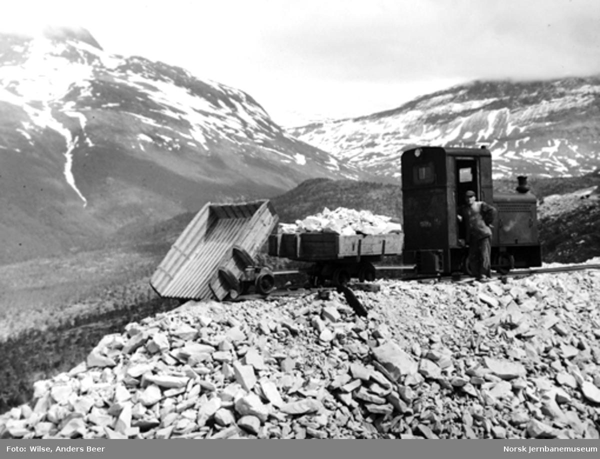 Anleggstog med steinmasser på tippen for Kjemånasen tunnel, Nordlandsbaneanleggets 13. avdeling, Storjord
