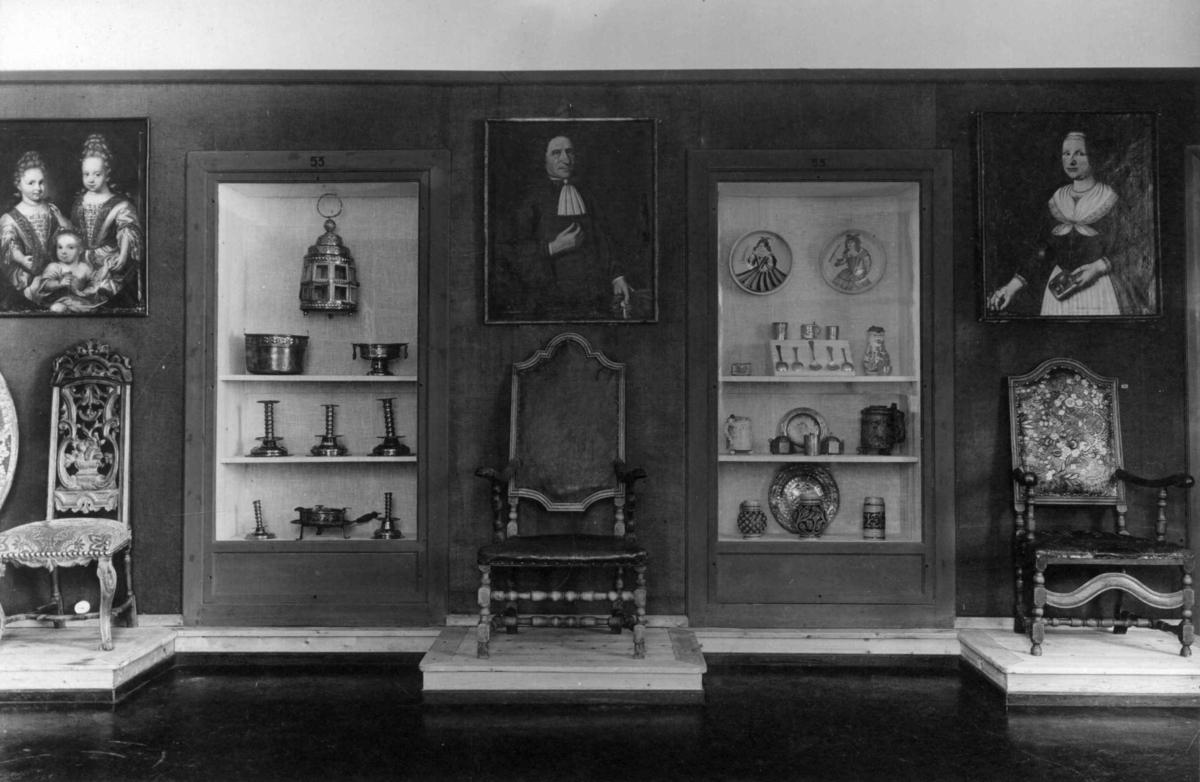Vegg med montere og stoler fra barokkrom slik som utstilt i Bysamlingen på Norsk Folkemuseum i 1923. Over stolene henger det portretter.