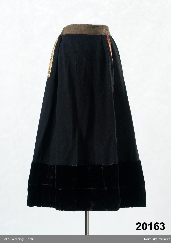 """Kjol kallad """" jöb"""" av svart kläde kantad nedtill med 24 cm svart ylleschagg, med invändig skoning av röd vadmal. Slät framtill, tätt rynkad bak, linning av brun bomullslärft s.k. domestik som baktill har ett påsytt svart sidenband med inbroscherat mönster med blommor i lila och gult. I höger sida en infälld ficka kantad med sidenband i gljusgult, grönt och rött. Sprund mitt fram kantat med rosa sidenband. Se Elna Mygdal. Amagerdragter. Kphmn 1930 /Berit Eldvik 2011-11-24"""