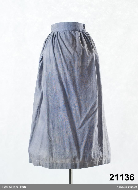 """Kjol, sannolikt underkjol, av ljusblå bomullslärft, sydd av tre raka våder, sprund i vänster sidsöm, slät framtill med vidden samlad bakåt i täta lagda veck, 5,5 cm bred midjelinning av tyget, knäppt med en liten hake och hyska. 3,5 cm bred fåll. Kjolen handsydd. Flammigt urblekt. Har enligt Huvudliggaren använts av Rättviksgruppen. Med denna menas Hazelius iscensättning  med klädda figurer i en Rättviksinteriör av  målningen """"Lillans sista bädd"""" av Amalia Lindegren målad 1858. Hazelius satte upp denna grupp dels 1877 i den nya utställningslokalen på Drottninggatan 79 och dels på Parisutställningen 1878, där den gjorde stor succé. Kjolen skall ha använts på den knäböjande kvinnan. Den ljusblå färgen är något märklig i sammanhanget. Kan  ha varit en underkjol? Jfr med kjolen 16.325 som stämmer bättre som kjol och är tillverkad och såld av samma person.  Pers- Brita var en av Hazelius """"kullor"""" i museet som uppenbarligen var med och iordningsställde panoramat och såg till att figurerna kläddes på rätt sätt. Hon var sedan med  i Paris och vaktade utställningen under flera månaders tid och kallades efter det """"Paris-Brita"""". Detta finns omskrivet av Sigfrid Svensson i Minnesbladet: Artur Hazelius 1833-1933, utgivet av Nordiska museet, 1933. Se även foto NMA 0032015. Lindegrens målning har inv.nr 297936 Se Fataburen 1980: Dräktdockor,-  Hazelius och andras;  av Jonas Berg, sid 9-27. Även bild i jubileumsboken Nordiska museet under 125 år, sid 277,  1998. /Berit Eldvik 2011-10-06"""