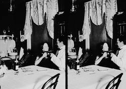 Interiør, mann og kvinne sitter ved bord og skåler, Axel Q.