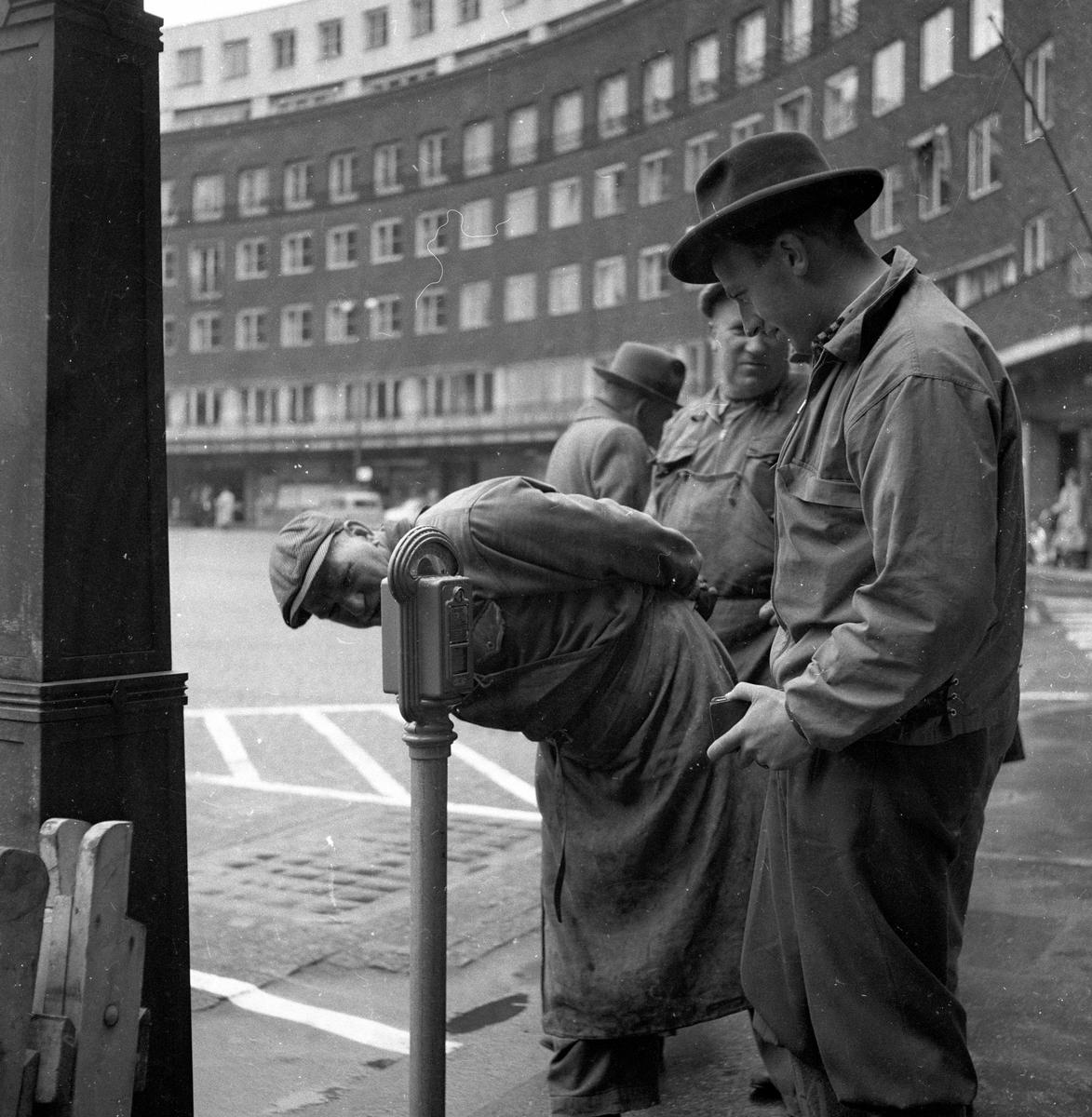 Menn studerer nytt parkometer på Fridtjof Nansens plass i Oslo.  Fotografert mai 1958.