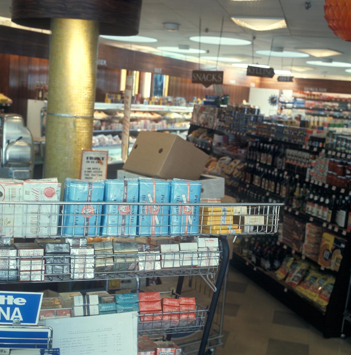Butikkinteriør. Hyller med tobakk i butikk.
