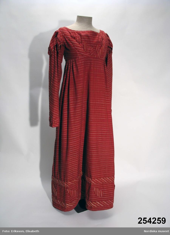 """Klänning i empirmodell av troligen hemvävt rött bomullstyg i tuskaft med invävda tvärgående mönsterränder i form av små sneda romber av silke i schatterande ljusgult, ljusgrönt och vitt. Det korta livet består av 1 framstycke och 4 ryggstycken, framtill med applikationer av tyget i form av vaddfylld """"löv"""" och snedremsor. Ärmen lång, snäv och skuren på snedden med likadana fyllda """"löv"""" i en rad vid handleden, över axeln en pålagd extra puffärm med flikig kant. Kjolen i 2 våder med breda sidkilar, slät mitt fram med vidden samlad bak i rynkor. I nederkant dekor av likadana fyllda snedremsor och något större """"löv"""" av avigvänt tyg, kjolfållen vadderad till en valk som håller ut och styvar upp kjolens nederkant. Knäppsprund i ryggen med 8 dolda hakar och hyskor och 4 små överklädda platta knappar som dekor, sannolikt saknas 4 knappar. Livet fodrat med oblekt linnelärft. Fastsydd tygetikett i fodret med handskriven text: """"Sydd för Eva Plagemann f. Åslund omkr. 1810"""". Av modellen att döma bör den vara sydd något senare omkr. 1820. Väl använd och trådsliten mitt fram i silkeränderna.  Eva Åslund 1785-1853 gifte sig 1822 med apotekaren Carl Johan Plagemann 1779-1864, efter att han blivit änkling 1816. Detta år grundade han också apoteket Nordstjärnan i Stockholm. Familjen är omtalad på flera ställen i Årstafruns dagbok. Eva Plagemann var mormorsmor till givaren Dora Lamm /Berit Eldvik 2009-08-25"""