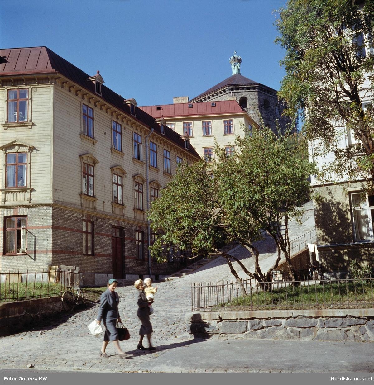 Göteborg. Trähus, kullerstensgata. Kvinnor och ett barn i förgrunden. Skansen Kronan.