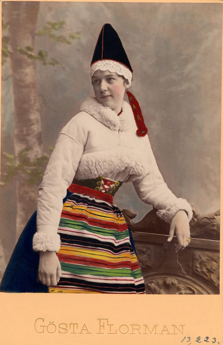 Ung kvinna poserar i folkdräkt från Rättvik i Dalarna. Kolorerat porträttfotografi.