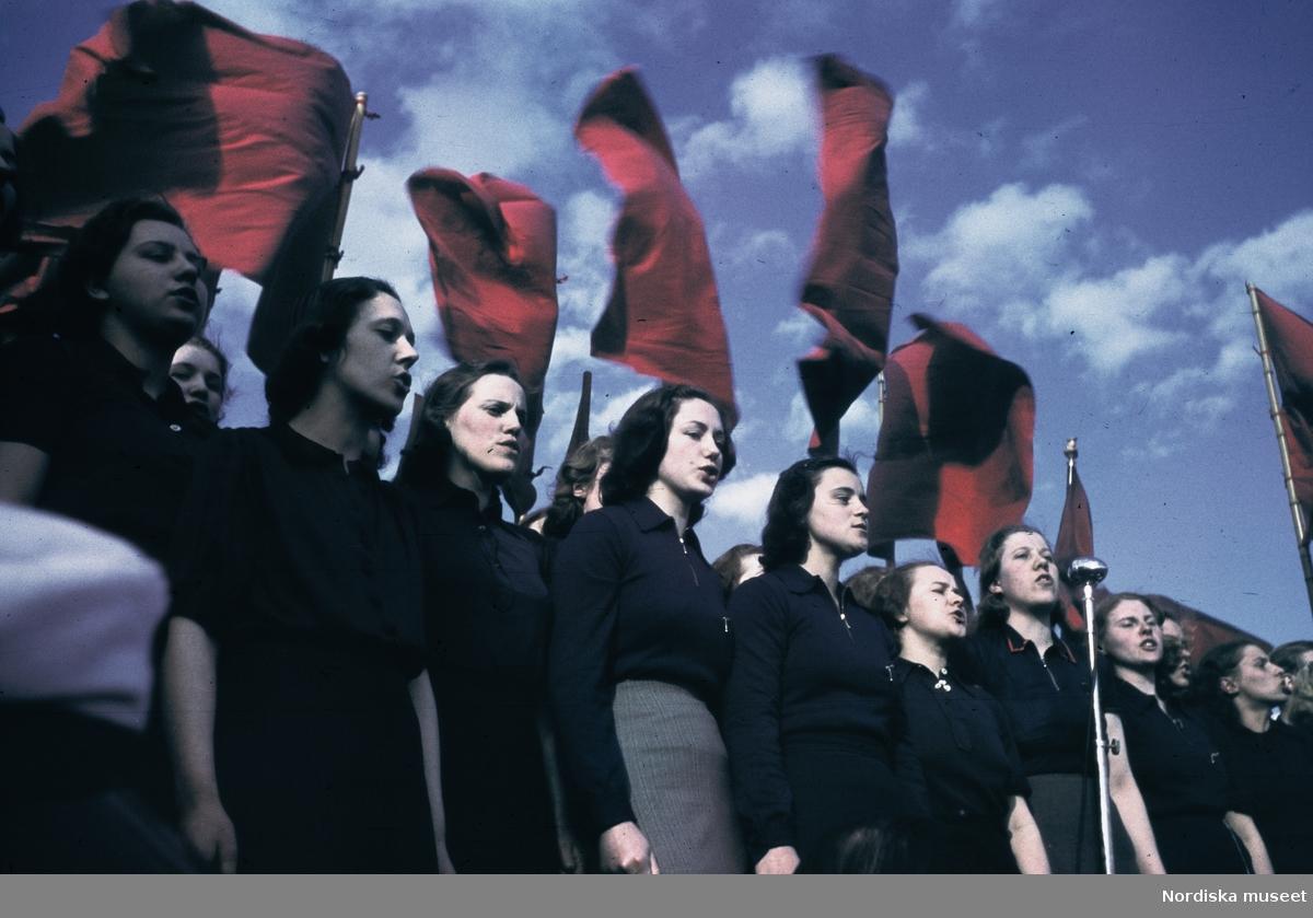 Röda fanor. Sångkör. Första maj, arbetarrörelsens demonstrationsdag.