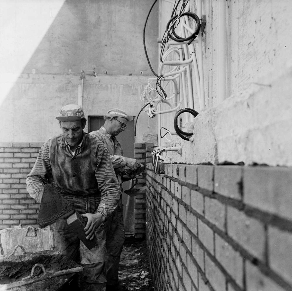 Kärvt för byggjobbare i Tierp, Uppland augusti 1972. Två män murar