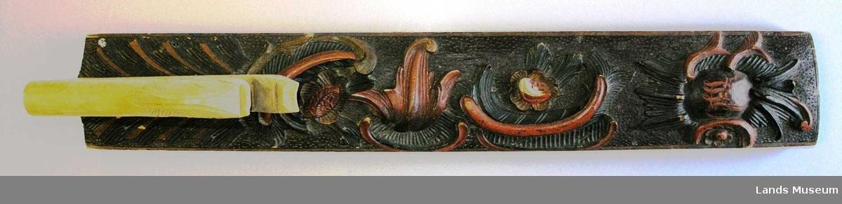 Mangletreet har rokokkoinspirert planteornamentikk og et innfelt, hesteformet håndtak, som er av nyere dato. Mangletreets overflate er malt, mens håndtaket er ubehandlet. Forenklet akantusranke, C-motiv, blomster, et kartusjlignende felt med påmalt skrift.