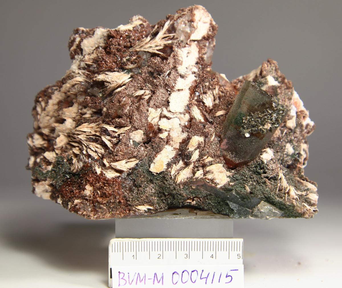 Baritt, hvit. Kvarts, kloritt, brunt mineral (kalsitt?), laumontitt, kalsitt, på feltspat?