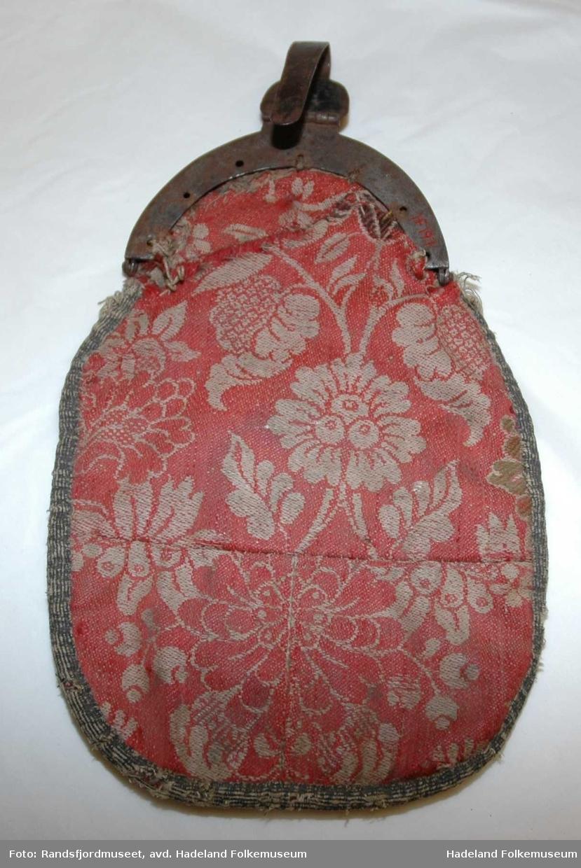 Kvinne. Veske med ulldamask med blomstermønster på bakside. Svart fløyel på framsiden. Lås og hempe.  Stoffet (damasken) er trolig gjenbrukt fra liv/vest. Brosjert kallemank