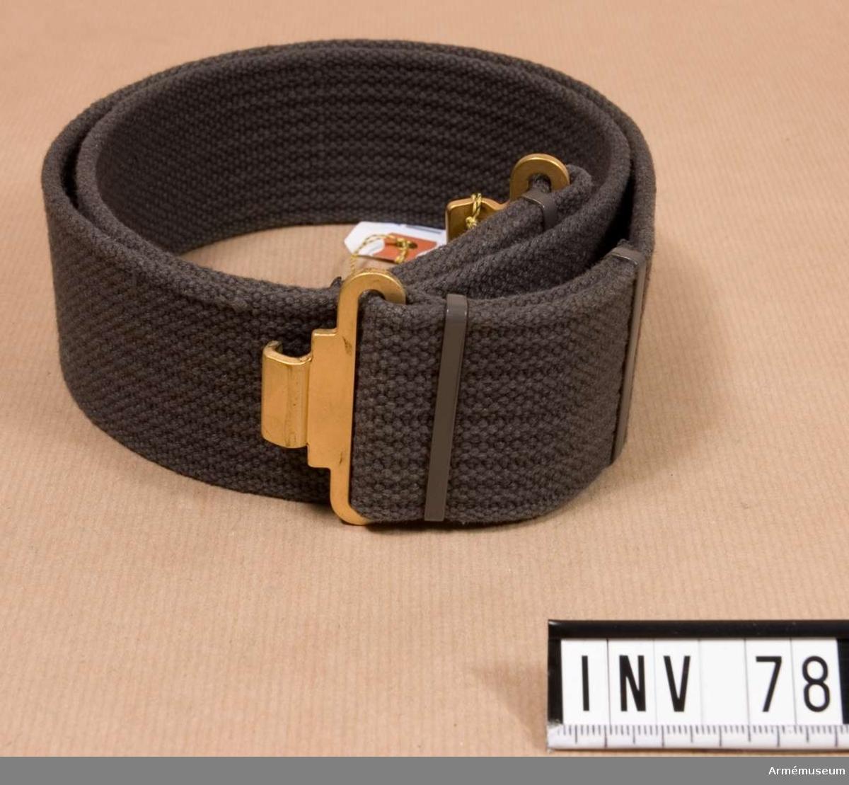 Samhörande nr är 1-119 (70-78, 119). Livrem m/1952: Av grå textil, bomull. Häktas fast med gulmetallkrokar. Har tillhört Gustav VI Adolf (1882-1973).