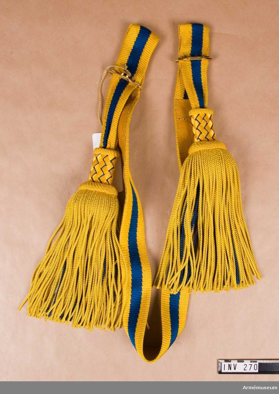 Rulla 1916. Längd utan tofsar: 1400 mm. Skärpet är gjort av blått och gult tvinnat silke. De yttersta ränderna är gula, c:a 15 mm breda, och den mittersta randen är blå i samma bredd. Skärpet är fodrat med ljust läder. Den stela övre delen av tofsen är flätad över trästomme, d v s gult silke spunnet över pappremsor 6 mm breda, och korgfläta tillsammans med blå snodd av silke. Stommen fortsätter något under övre delen av tofsen för att föra ut denna. Stommen är då något vadderad och överklädd med blå satin. Tofsarna av tvinnat silke består av ett inre lager blått och ett yttre av gult  silke. Spänne försett med hakar för att reglera skärpets vidd. Guldmetall.