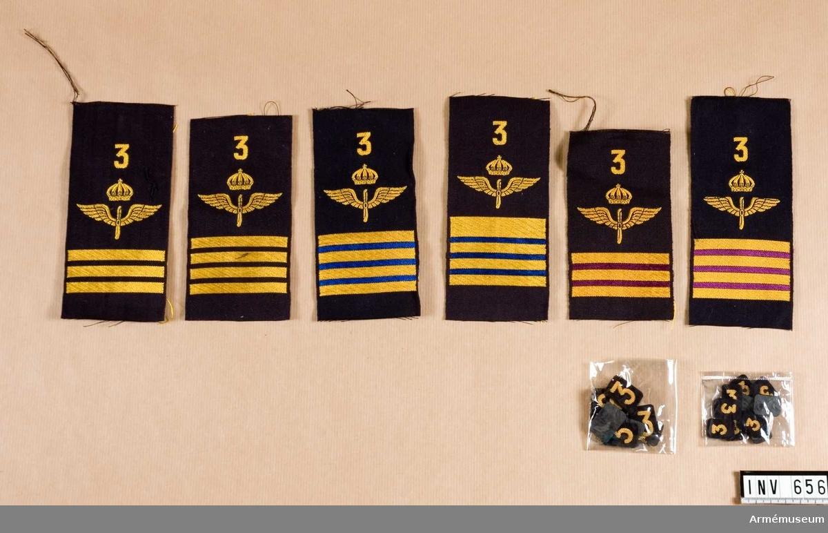 Låda m flygemblem m/1930. Innehåll: Flotilljsiffra 3, 18 mm hög, 100 st, (5) 10 mm hög, 100 st, ärmemblem för överfurir (fyra större streck) 100 st, ärmemblem för furir (tre större streck) 100 st, överfurir teknisk personal (fyra större streck med violett färg emellan), furir (tre större streck med violett färg emellan för teknisk personal) 100 st, Överfurir flotilljpolispersonal (fyra större streck med blå färg emellan) 100 st, rustmästare flottiljpolispersonal (fyra jämna stora streck med blå färg emellan) 100 st.