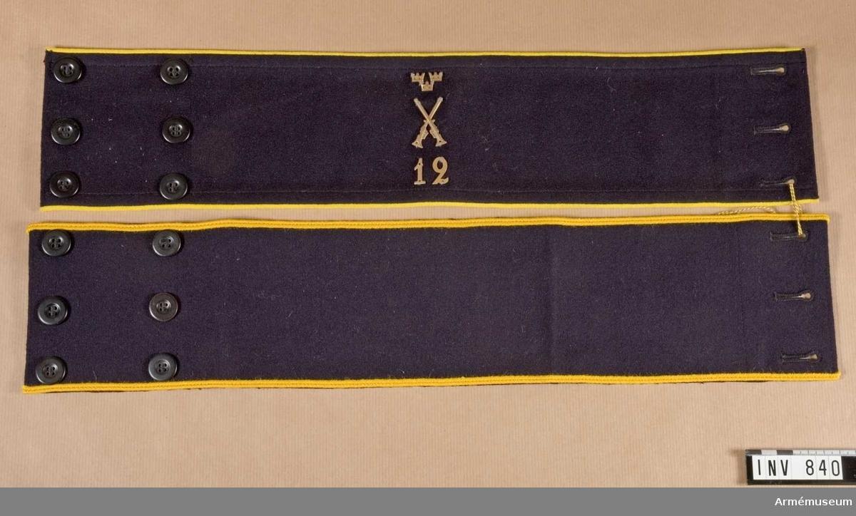 """Armbindel m/1939 (eller tidigare), Arméledningen. Av mörkblått kläde med gul passpoil. Ena sidan försedd med tre knapphål, maskintränsade och förstärkta på baksidan med en lärftbit över hela bredden. På motstående sida två rader knappar med tre i var rad. Knappen är av mörkblå konstharts. Under dessa sitter en förstärkning av lärft. Mitt på bindeln arméledningens emblem. Underst """"12"""", däröver infanteriets emblem och däröver tre kronor, allt i bronsfärgad metall och fastsydda med tråd. Använts av civil personal.  Samhörande nummer är AM.000838 - AM.000843."""