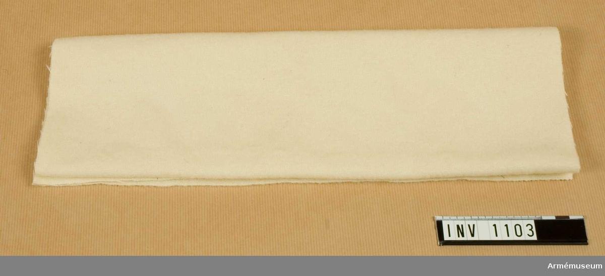 Samhörande nr är 1074-1129, 8240 (1102-1103).Fotlapp m/1895.Av vitt uppruggat ylletyg i tuskaft. Användes i skodonet, att svepa runt foten. Har tillhört mob.utrustning vid Armémuseum.