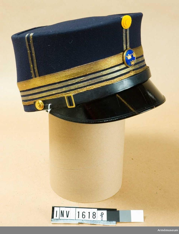 """Stl 59. Av mörkt blå yllediagonal med svart lackskärm och mössrem. Remmen knäppes fast nedtill på mössans sidor på kullen, med Gst:s knapp m/mindre. Två korslagda marskalkstavar som emblem. Remmen har ett litet fyrkantigt spänne. Däröver tre smala guldgalonband och ett 70 mm brett guldgalonband över det. Grad för överste. I mitten officersknapp av guld med framsida av blå emalj och tre guldkronor. Sidenkokard vid kullens kant. Stolpar av guldgalon mitt fram och bak, på var sida. Ljus svettrem av läder och svart sidenfoder. Kullens foder märkt """"MEA""""."""