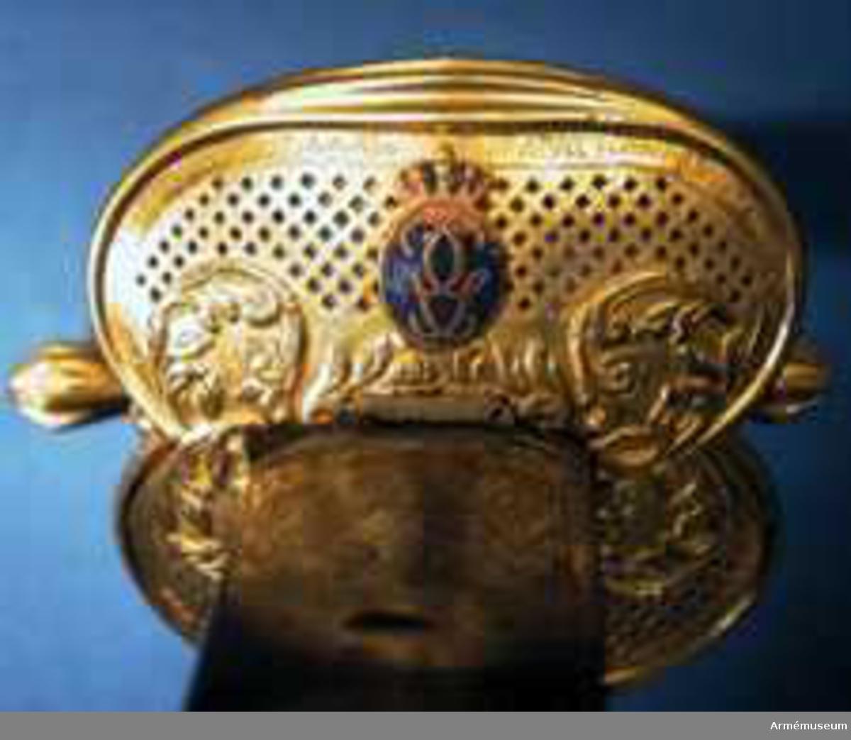 """Förgyllt fäste av kommendertyp med fyra medaljonger av blå emalj med Gustaf III:s krönta namnchiffer. På parerplåtens undre ytterkant är graverat """"Gifvit av Konungen til Fend.Örn för visad mandom mot Rikets Fiender 1790 under Kriget mot Ryssland.""""   Klinga av colichermardetyp med blånerad och etsad dekor med spår av förgyllning.  Bredd vid fästet: 33 mm."""