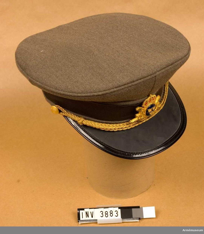 """Med mössmärke m/1951 f off och mössrem m/1952 för generalsperson/regementesofficer. Stl 57. Av gråbrungrön kamgarnsdiagonal. Modellen i överensstämmelse m mössa m/1939, se AM.003863 - dock m följande avvikelser. Rakare skärm, mjukare kulle och ett grått mössband av rayonsiden runt stommen. Ingen galonpasspoal runt kullen. Mössmärke m/1951, se AM.004660. Två sidoknappar f off/uoff av liten knapp m/1952 f fast anställd off/uoff (förbands-/personalkårsknapp) och ej som i modellprovet knapp m/1952 liten m tre kronor, vilken anläggs av furir/överfurir. Samtliga knappar och övriga tjänstetecken t uniform m/1952 utförda i metallfärg m/1952 guld, se AM.004664. På foderkullen fastsydd plastfolie f skydd åt fodret. Märkning i fodret. Vävd etikett anger tillverkaren ACB samt storlek. Äganderättsmärkning, tre kronor, stämplat på fodret. Vidhängande etikett anger fastställelsedag. """"Stockholm den 26.mars 1953 Torsten Nilsson C Årman""""."""