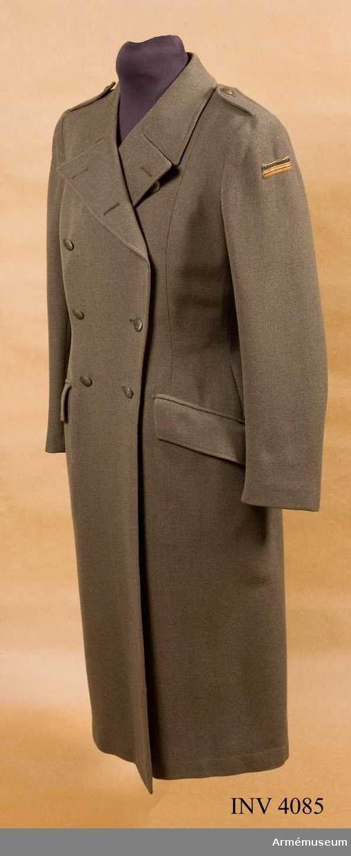 """Ylle. Storlek 42. Kappa m/1942kv, Riksföreningen Sveriges Lottakårer, SLK. Av gråbrungrön kamgarnsdiagonal, figursydd med  dubbelknäppning med fem par knappar m/1939 av armens modell,  bronsfärgad, märkt Sporrong. Slag som går att knäppa ihop och  axelklaffar fastsydda med ärmsömmen och fastknäppta med SLK:s knapp. I ryggen slejf, knäppt med två knappar. Sprund. På  vänster ärms överdel chefslottamärke: en bred guldgalon, en smal blå silkesnodd och en smal guldsnodd. Insydda fickor med  raka lock. Kappan är fodrad med grått konstsidenfoder och i  """"nacken"""" finns en bandetikett med namnet RUDEBECK ."""