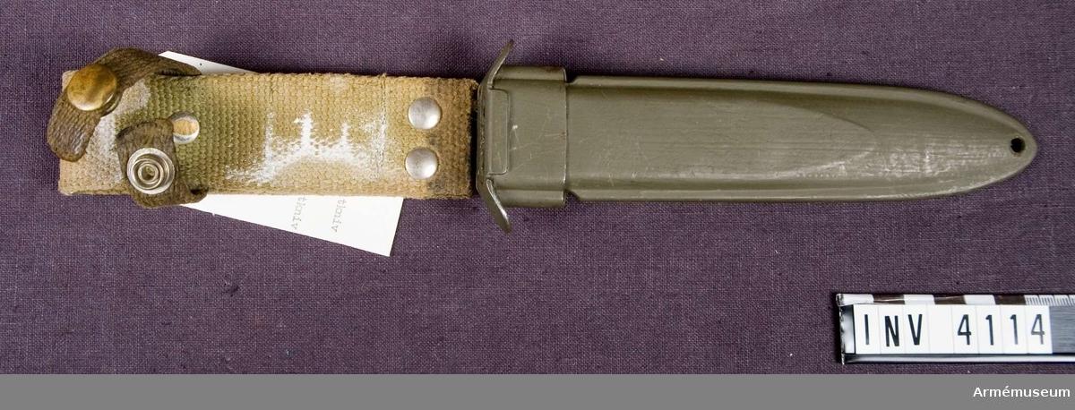 Samhörande nr är 4113-4114.Balja m/1954 t fältkniv fm/1954.Av konstmassa. Lackerad med olivgrön färg. Baljans l utan bäranordning: 185 mm. Bäranordning av väv.