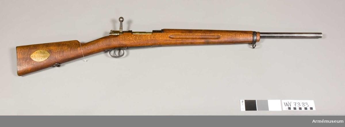 Gevär system Mauser, liknar fm/1923 med förkortad pipa, kaliber 8 mm och tändstiftsmuttern förkortad. Kaliber 8 mm. Tillverkningsnr 12/41, märkt GB.Mekanismens tändstiftsmutter förkortad. Riktmedel saknas. Förstocken förkortad. Läskstång saknas. På kolvens högra sida finns en märkbricka av mässing ( NR 12/41 Normal 2 Korr + 4 ).