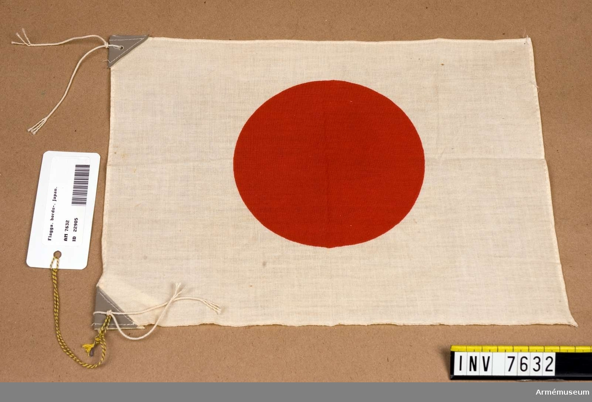 Vit bomullsflagga med en röd platta (tryck) i mitten.   I de inre hörnen är hörnen förstärkta med grå plast (pegamoid?) vari det finns hål för snodd för upphängning.