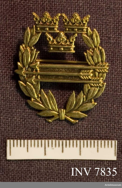 Av guld. Höjd 32 mm. Bredd 25 mm. Ett ovalt guldmärke med lagerkrans med på mitten tre pilar och upptill riksvapnet (lilla).