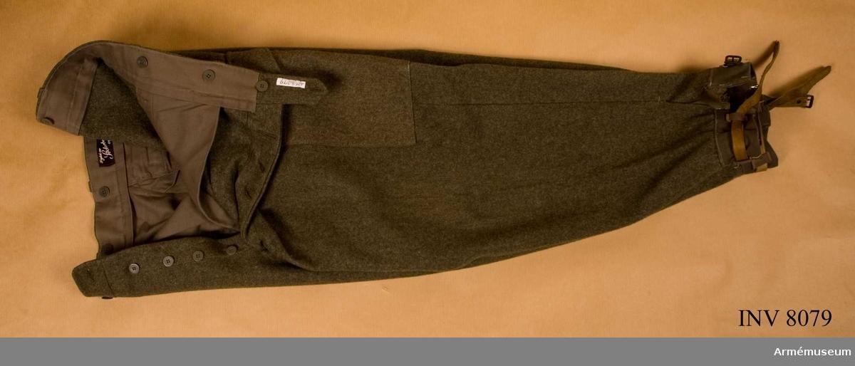 Längd 760 mm. Midja 1000 mm. Färg gråbrungrön. Storlek 104. Tillverkade av gråbrungrönt kommisstyg. Har fasta damasker och två framfickor, två benfickor, en bakficka och hällor för  bälte.
