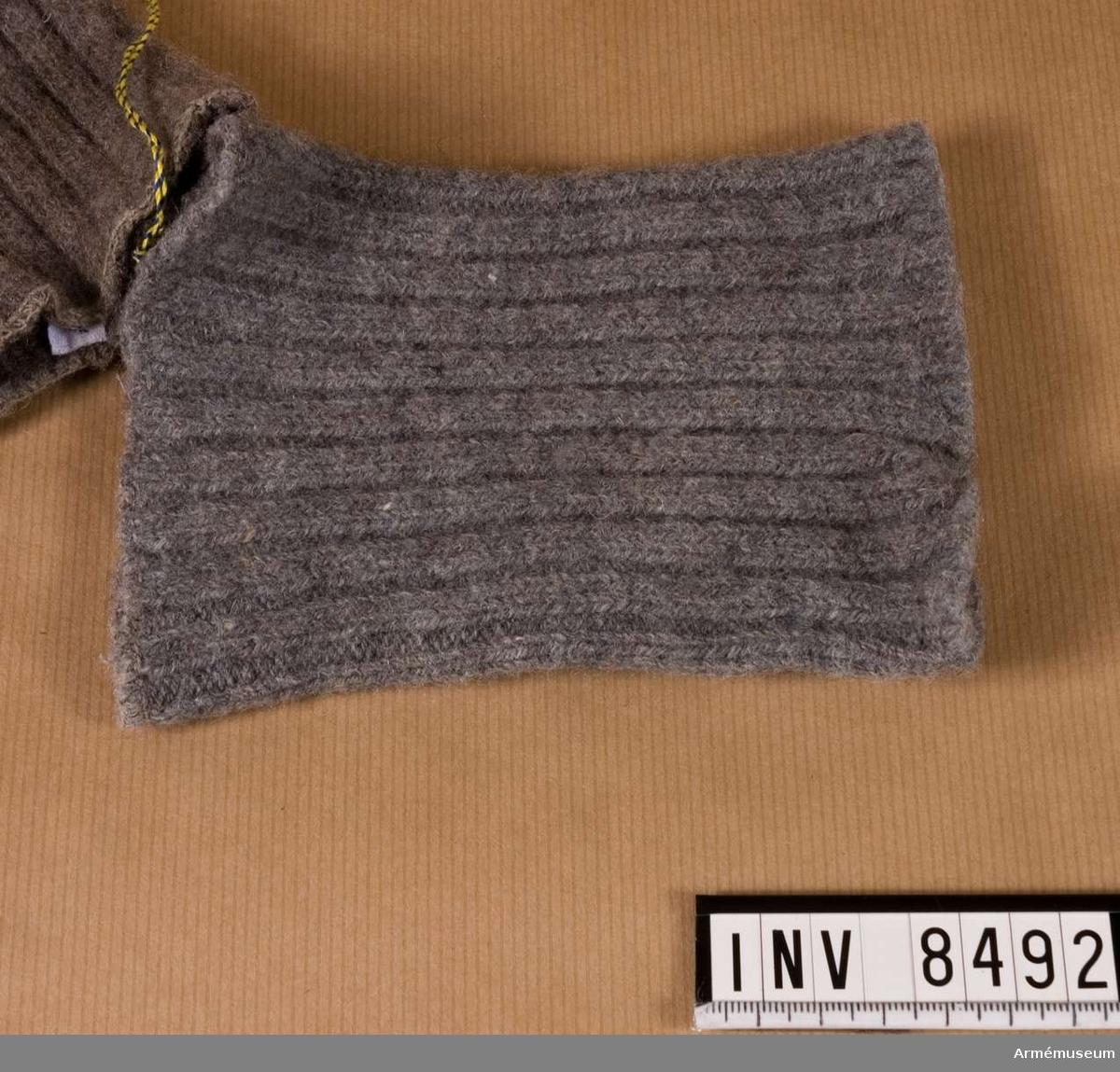 Samhörande i par 8491-2. Stickad i grått yllegarn, två aviga och två räta maskor. Stickad som en mudd som sytts ihop ett stycke in i nederkanten, så att det bildats ett hål för tummen. På så vis täcker mudden halva handen och hålls samtidigt på plats.