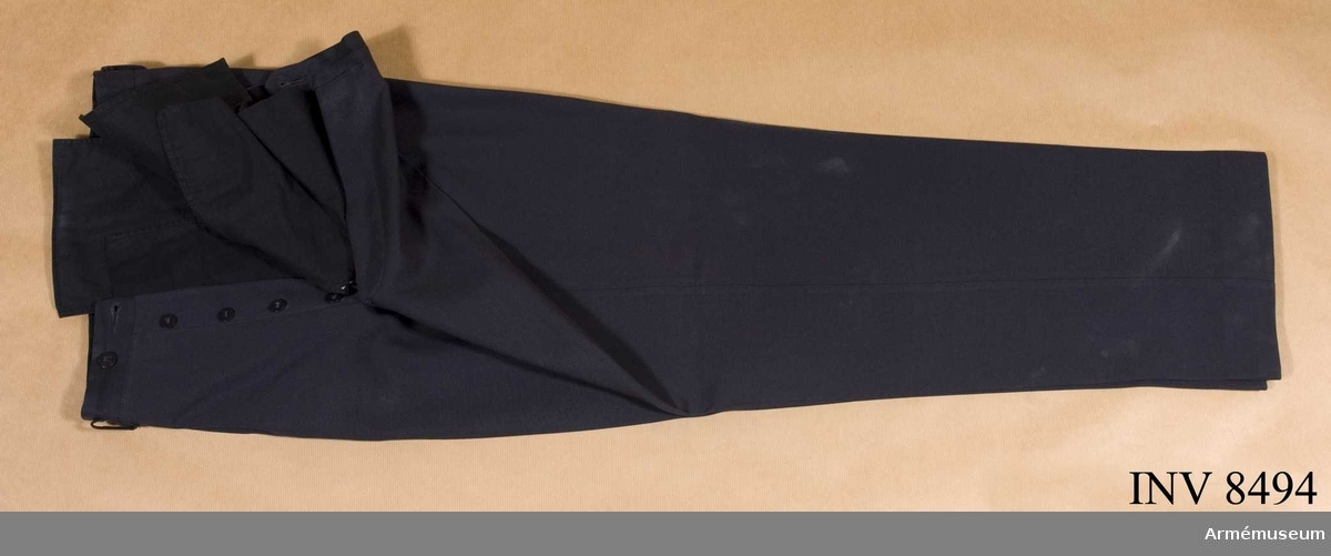 Tillverkade av stålgått ylletyg, är utan uppslag, har två raka sidfickor och två bakfickor samt hällor för bälte. Byxorna är märkta: Svensk TeBeWe kvalité. Källa Uni A 1960 24:21-23.
