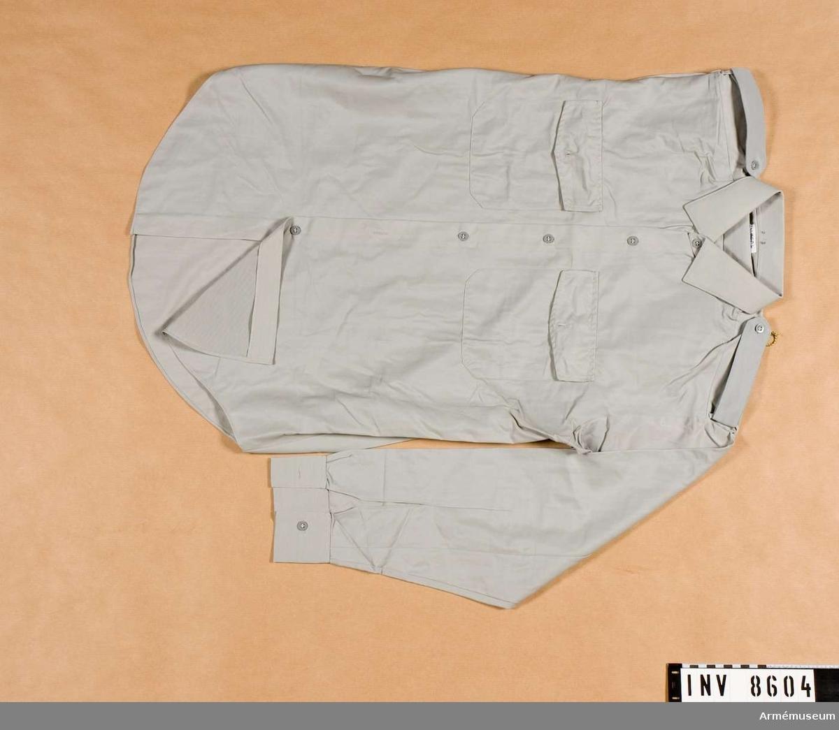 Skjorta m/1960.Tillverkad i gråblått tyg, har fast krage, lösa axelklaffar, två bröstfickor med lock och knapp samt knappar i tygets färg. Storkek 39. Källa Uni A 1960 24:25.