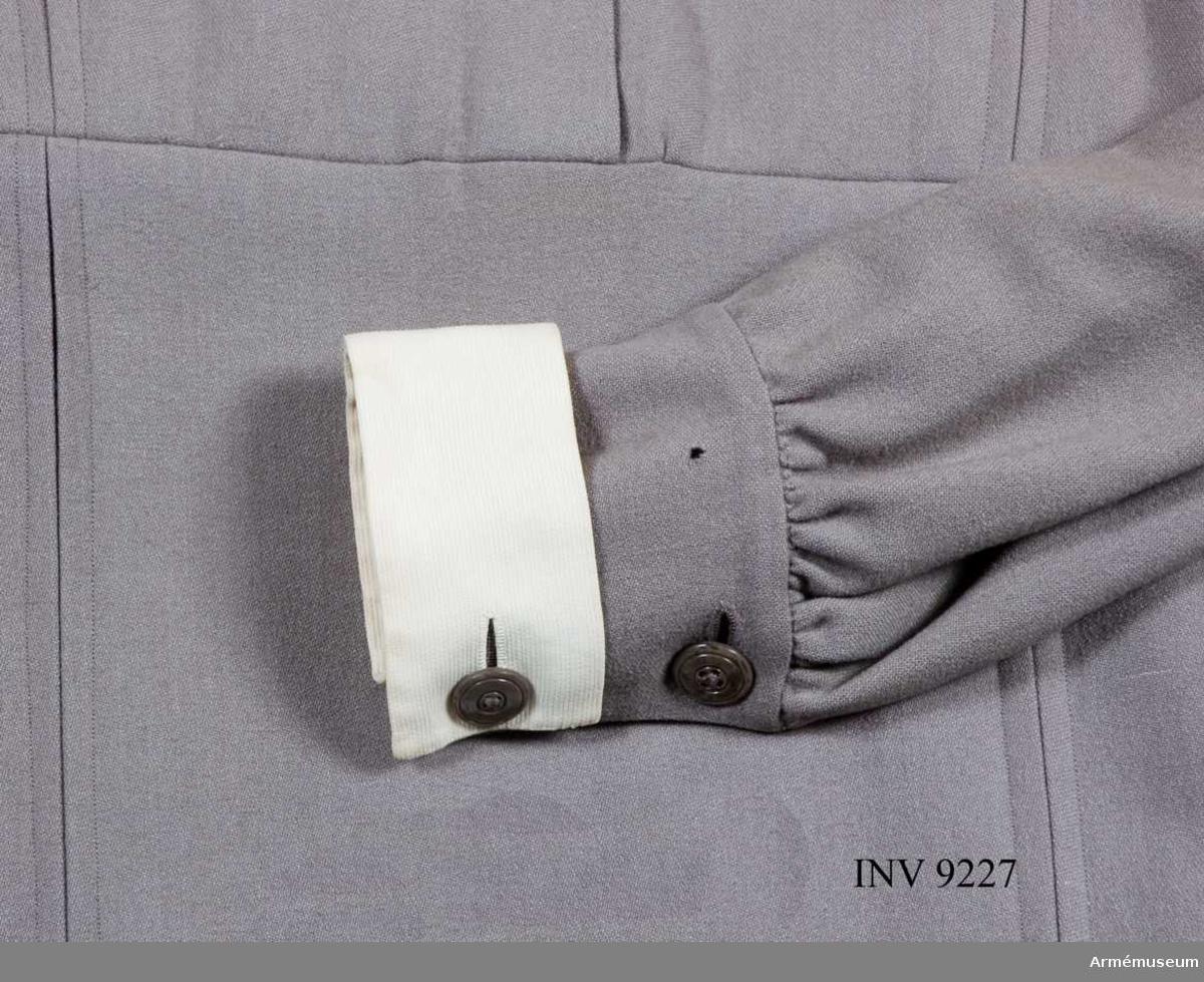 Av ylletyg i samma kvalitet och färg som klänningen. Den är  fodrad med flaggduk som går fram som en passpoal på långsidorna. Den är ihopsydd under ärmen och skall fästas på vänste ärm alldeles under ringningen. Framsidan är broderad  med bokstäverna S L K i blått silke.  Samhörande AM.9223, 9225 - 9227