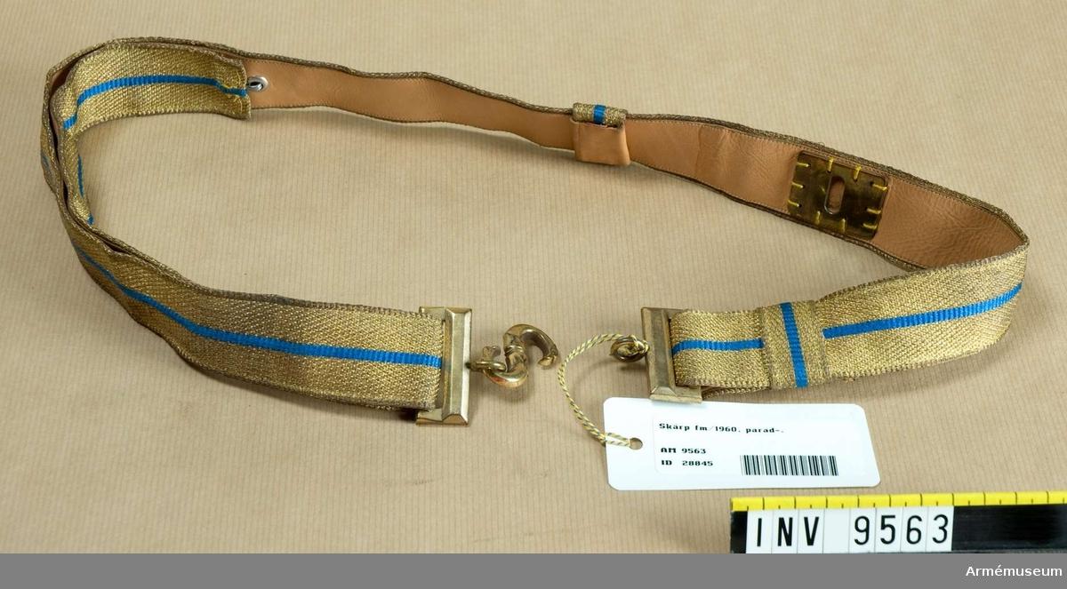 Tillverkat av gult och blått silke och med spänne av metall i guldfärg. Skärpet är fodrat med naturellt skinn.