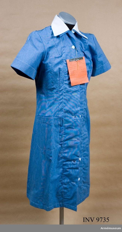 Av blåmelerat bomullstyg med knäppning framtill och med hällor på axlarna för förklädesbanden. Klänningen har en vit påknäppt krage.
