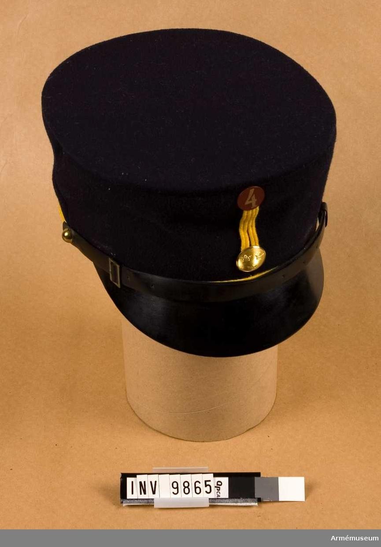 """Tillverkad av mörkblått kommisskläde med gult snöre runt kullen och med agraff i samma material. Mässingsknapp, räfflad med tre kronor och kompanimärke m/1951. Det är av metall målat mörkrött och med en """"fyra"""" målad i guldfärg. Mössan har svart lackskärm och mössrem i svart lackskinn. Vid sidorna kulknappar (halvknappar). Fodret är i svart vaxduk och har märkning i botten enligt följande: A 2 1939. II 58."""