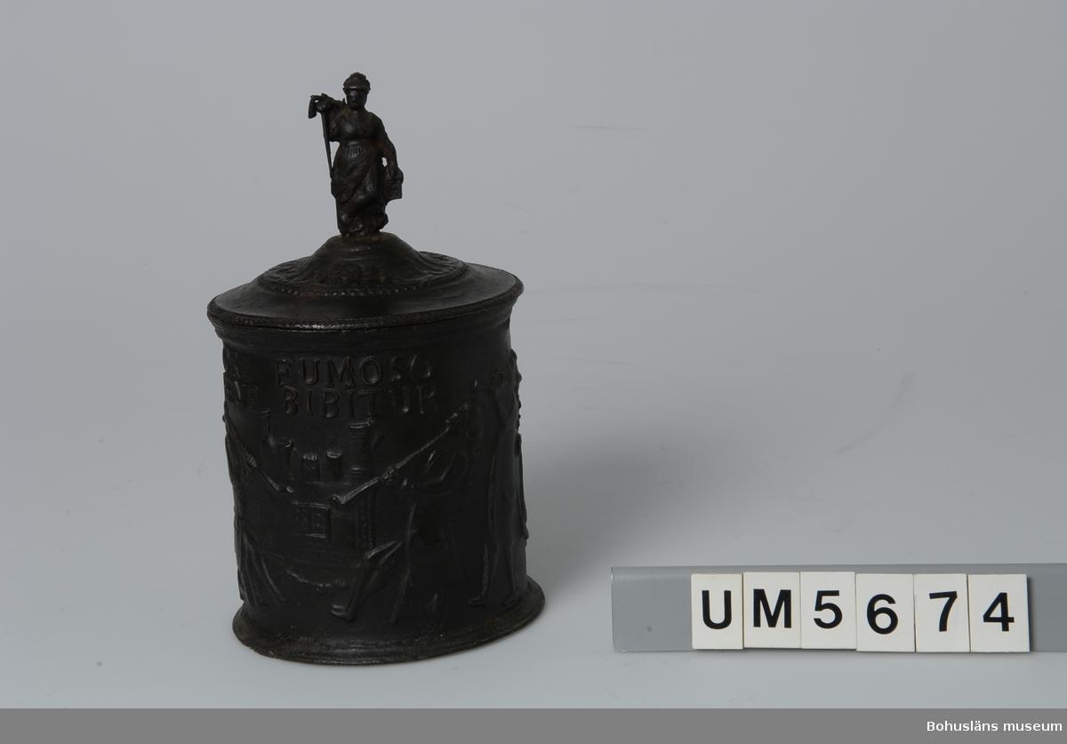 """Föremålet visas i basutställningen Uddevalla genom tiderna, Bohusläns museum, Uddevalla.  Gjuten cylindrisk form med lock, där lockknoppen utgörs av en kvinnofigur. På insidan av locket järnbrukets stämpel HF. i en ring. Texten """"ORE FUMOSO BENE BIBITUR"""" (""""Man dricker bra medan man röker"""") i upphöjd relief på burkens ena sida; på motsatta sidan ingjutet """"O:G:L: 1793"""". Fyra musicerande respektive rökande män, ett bord med dominobitar/del av ett spel, dryckeskärl, två lejon och en krona  pryder i högrelief utsidan. Tobaksbruken är tillverkad vid Hellefors järnbruk i Södermanland.  Ur handskrivna katalogen 1957-1958: Tobaksburk Bottenmått (diam.) 13,4 H (med lock) 23,5. Av järn med figurer och inskrift. Föremålet. Rostad.   Lappkatalog: 95"""