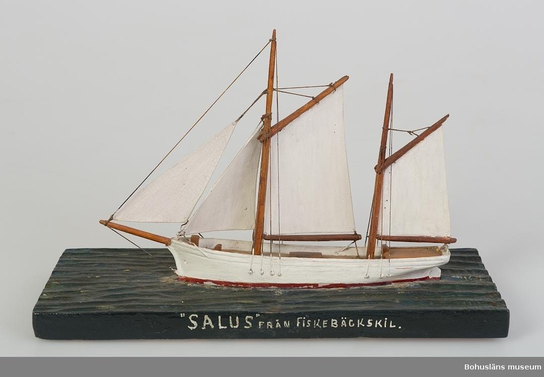 """594 Landskap BOHUSLÄN 503 Kön MAN 394 Landskap BOHUSLÄN  Skepp med två master. Vitmålat skrov. Monterat på en rektagulär träplatta formad till att se ut som hav. Text på ena långsidan av plattan: """"SAULUS"""" FRÅN FISKEBÄCKSKIL.""""  Ur handskrivna katalogen 1957-1958: """"Salus"""", Fiskebäckskil Modell på platta. L. från för till akter: 17,5. Föremålet helt. Från kapten Olssons saml., Fiskebäckskil.  För ytterligare information om förvärvet, se UM5087."""