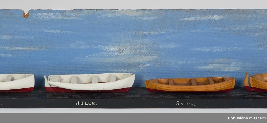 """594 Landskap BOHUSLÄN 503 Kön MAN 394 Landskap BOHUSLÄN  Sex båtar fastsatta i en rad på en blåmålad bräda. Under båtarna på brädans ena långsida står namnet på båttypen: """"SKEPPSEKA, GIGG, JULLE, SNIPA, KÅG WESSING, LIVBÅT"""". På baksidan brädan (i fonden) är det fastsatt en blåmålad skiva av träfi  Ur handskrivna katalogen 1957-1958: Sex livbåtsmodeller Modeller av skeppseka, gigg, julle, snipa, kåg-vessing, livbåt, på platta. Plattans mått 124 x 5,5, Föremålen hela. Från kapten Olssons saml., Fiskebäckskil.  För ytterligare information om förvärvet, se UM5087."""