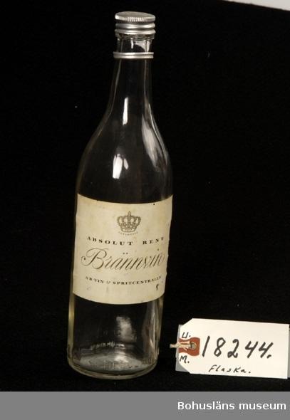 """Föremålet visas i basutställningen Kustland,  Bohusläns museum, Uddevalla.  594 Landskap BOHUSLÄN  Enliters butelj i brunt glas med skruvlock för sprit.  Etikett för """"Reymersholms Kron - Brännvin""""."""