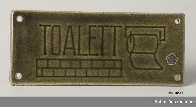 """Grönglaserad skylt med fyra skruvhål med inpressad dekor av ordet """"Toalett"""" samt toalettpappersrulle och murverk. Sign. med påklistrad femkantslapp i rött o. guld med kruka och ordet """"SYCO Keramik""""."""