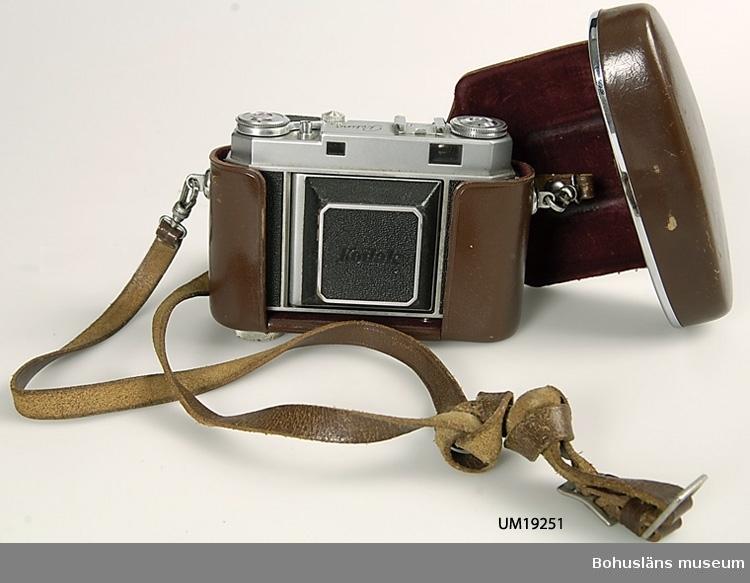 """Kamera av märket Kodak.""""Kompaktmodell"""". Småbildskamera 24x36 mm, med bälg. Fodral i brunt läder med rem medföljer."""