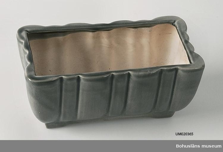 Rektangulär kruka, gråglaserad yttersida med en typ av grov godronnering. Signatur intryckt godset i botten.