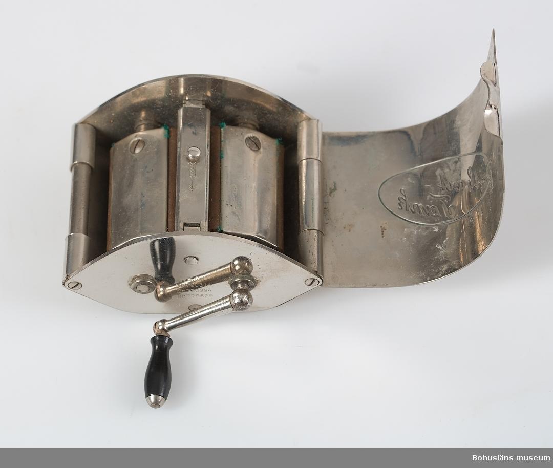 """Ovalformad hylsa med inneliggande fäste för rakblad och två valsar med läder och vev. Avsedd att slipa rakblad. På utsidan i relief inom oval med text: """"Potbart Tank"""". Se bilaga. Givaren Mariann Hedman  är dotter till Vilma (Wilma) Börjesson (1906-1986), och Kjell Börjesson (1905-1965),  innehavare av affären """"Kjells Herrkläder"""" i Lysekil. Till gåvan hörde även broschyrer mm som nu finns i museets Enskilda arkiv och böcker,  se biblioteket. Se även UM022370-UM026378 från samma givare."""