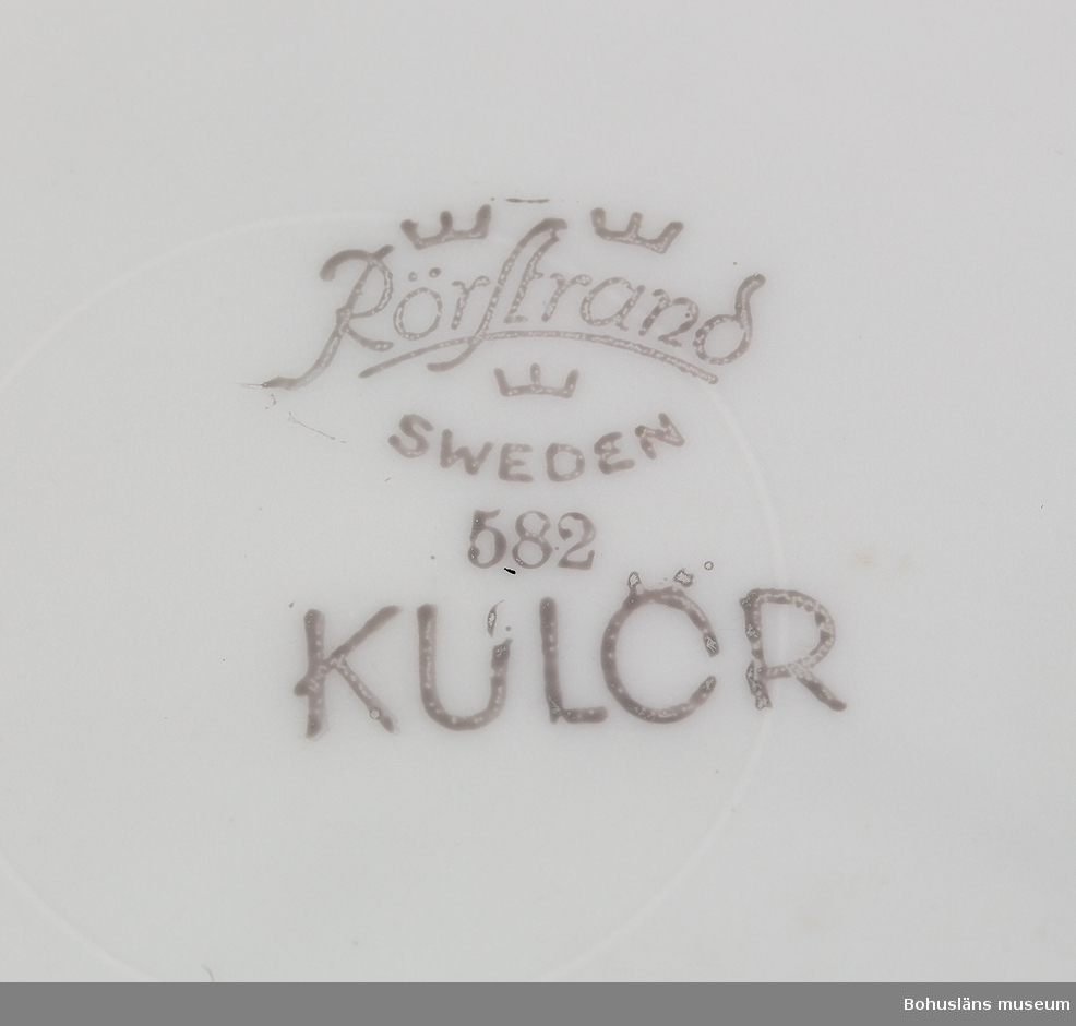 """Kopp, asymmetriskt placerad på kombinerat fat och assiett, s.k. """"TV-kopp"""", lanserad under 1950-talets slut, efter att teve införts 1956. Koppen har dekor av blå rundlar med svarta streck i fyrkanten över. Fatets botten märkt: """"Rörstrand, Sweden 582 KULÖR."""" Koppen omärkt."""