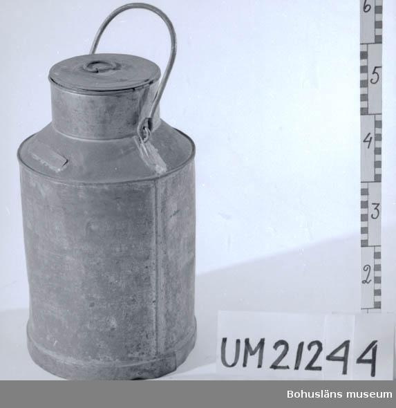 """594 Landskap BOHUSLÄN  Cylindriskt kärl med en smalare, kort hals. Lock och bärhandtag. Mässingsskylt med instansad text: """"HASSELBERGET"""".  Föremålet är något buckligt och korroderat.  Omkatalogiserat 1997-01-10 GH.  UMFF 3:11"""