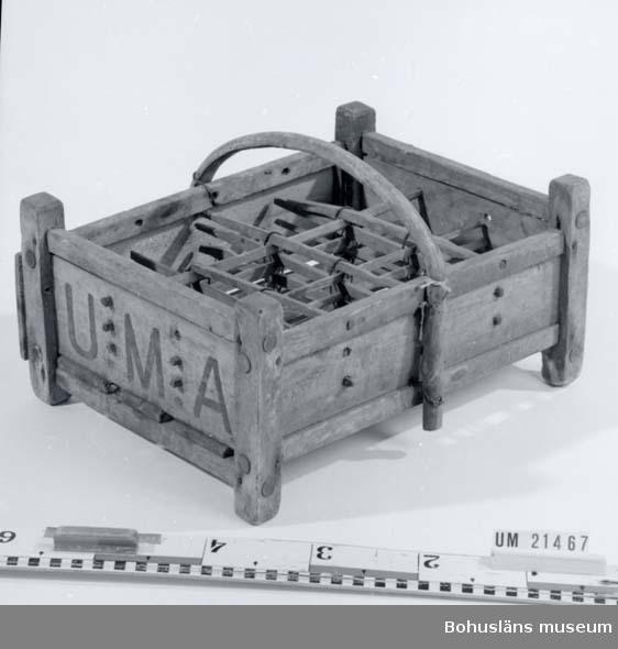 """594 Landskap BOHUSLÄN  Flaskställ för 12 flaskor. Gavlarna märkta med svart färg """"U.M.A."""" (Troligen """"Uddevalla Maltdrycksaffär""""). Facken tillverkade av träribbor hopnajade med ståltråd.Trähandtag.  UMFF 23:4"""