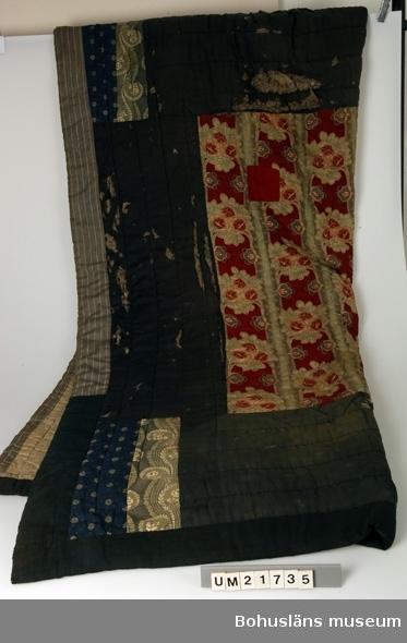 Lapptäcke för säng, både dekorativt och värmande, av stora tygbitar, ihopsydda för hand. Bård av blågrått ylle med remsor av svart/vitt bomullstyg längs lånsidorna och blågrönt ylle längs kortsidorna. I hörnen remsor av blått och ljusgrönt mönstrat bomullstyg. Mittspegel av tryckt blommigt jugendinspirerat bomullstyg i rött, ljust gulbeige, mycket ljust blågrönt och ljust rödbrunt. Foder av ljusbrunt bomullstyg. Vadderat med raffelstopp (gamla kläder som klippts i bitar och rivits upp till stoppning). Stickningar i ränder, diagonala på mitten. Yttersta kantremsorna påsydda sekundärt. Mycket slitet, stora revor runtom i bården, hål rakt igenom på mitten. Stor fläck vid ena långsidan. Blekskador. En lagning med röd lapp.