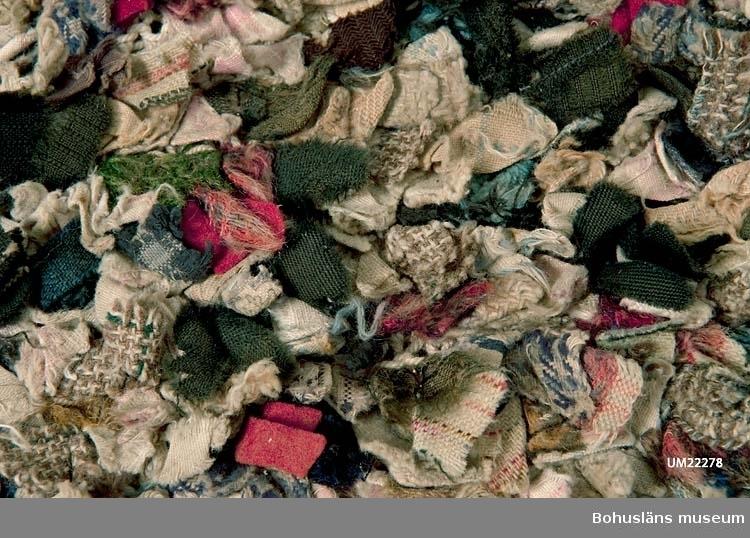 Tillverkningstid: Troligen 1900-talets början. Användningstid: Troligen 1900-talets första hälft.  Stickad botten av bomullsmattvarp (oblekt), kulörta ylle-, linne-, och bomullstrasor inlagda alternativt insatta i bottenmaterialet. (Man kan antingen välja mellan att lägga in trasor medan man stickar alternativt sätta in dem i den färdiga botten.)  Runtom i två lager, halvsfäriskt formade yllelappar av olika kvaliteter, påsydda, överlappande varandra. Lapparna langetterade runtom, broderat blommotiv i mitten av varje lapp.  Mattan fodrad med ett blågrått bomullstyg.  Nött, skador av användning, en bristning i fodret.  Se bilagepärm UM22278: Beskrivningar ur IDUN nr. 50/1889; John Hinchcliffe, Angela Jeffs, Trasmattor, Forum 1978.  Litteratur: Kerstin Ankert/Ingrid Frankow. Den svenska trasmattan - en kulturhistoria, Prisma 2003.